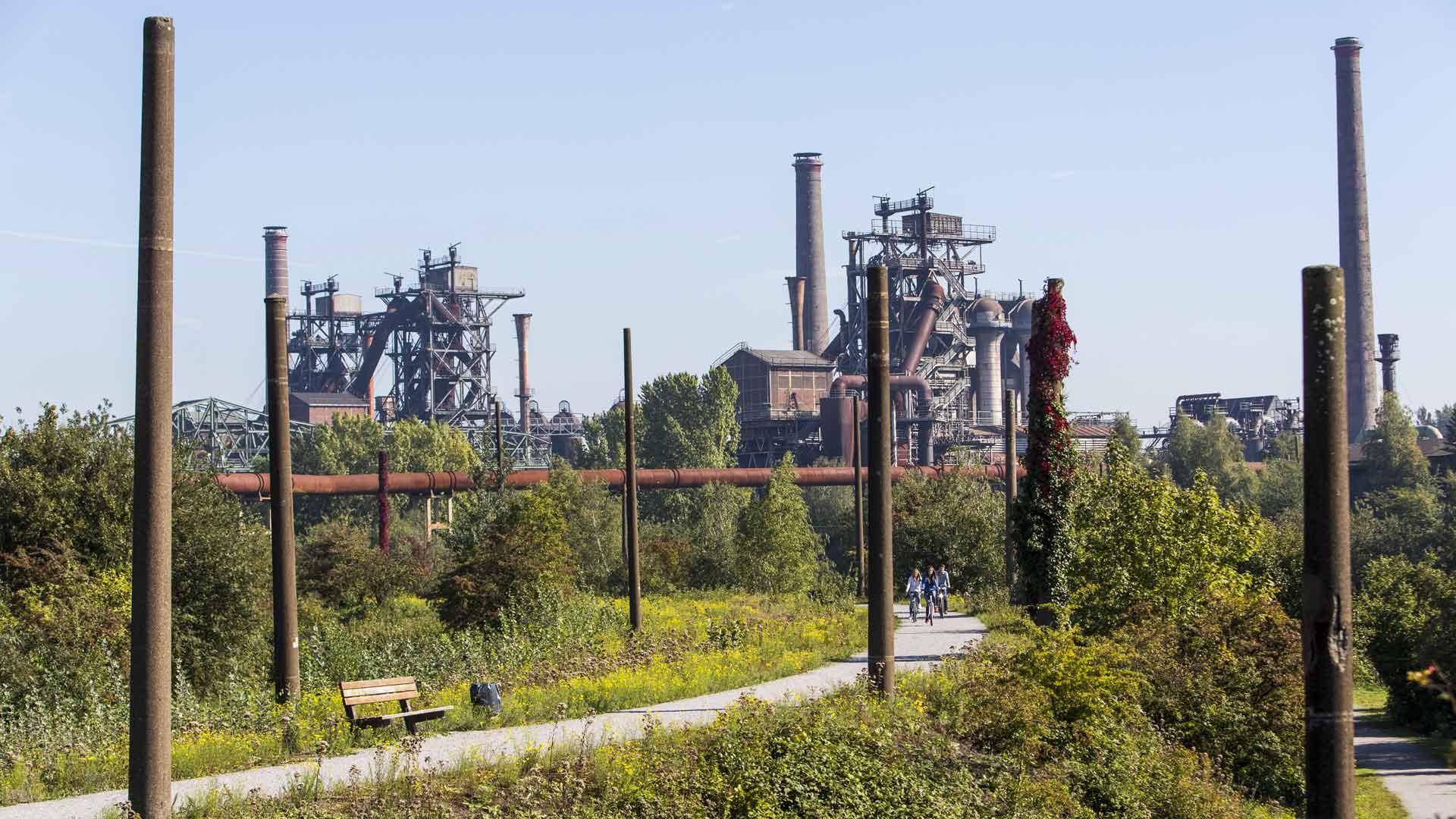 Fietsen tussen het industriële erfgoed in het Landschaftspark Nord in Duisburg. n_Tack