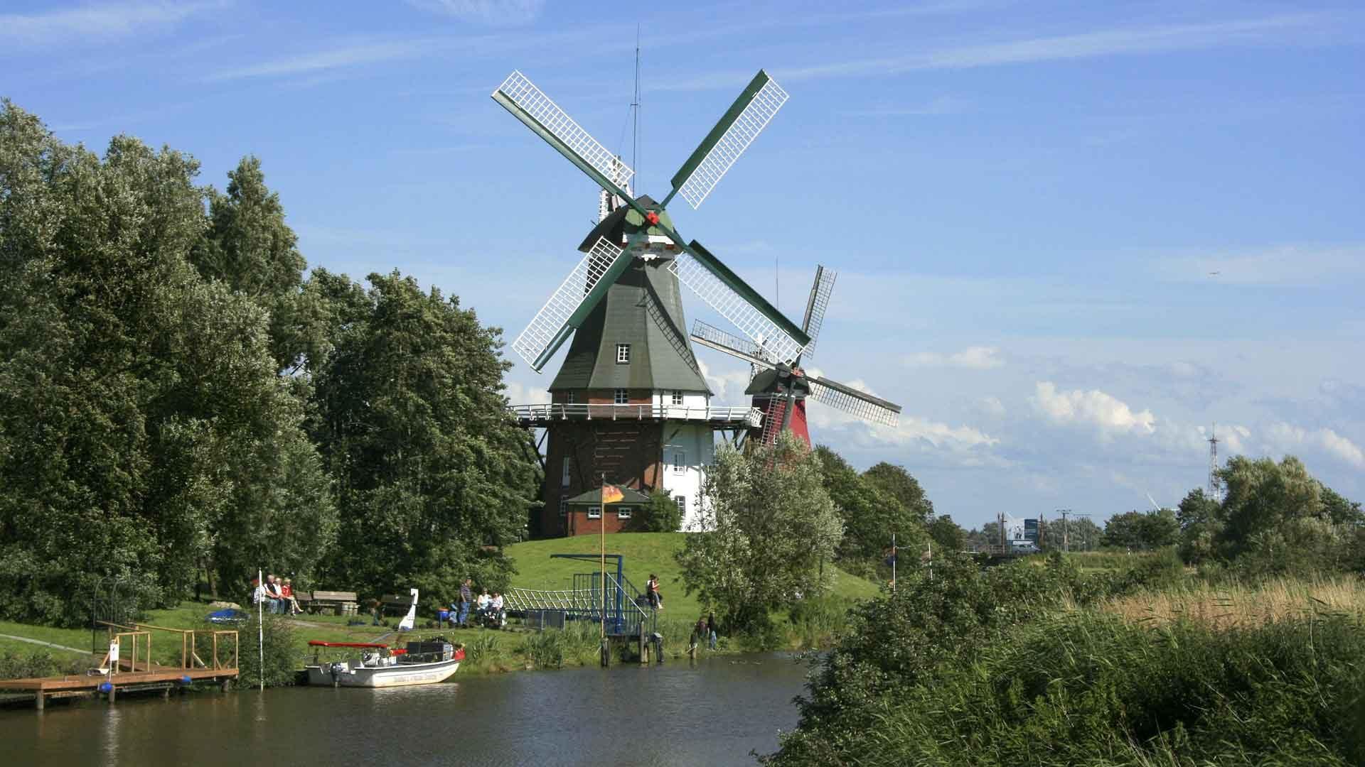 Fietsen langs weilanden, kanalen en molens in Ostfriesland.