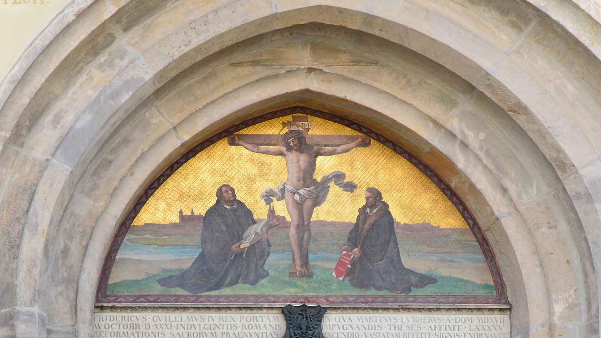 Luther en Melanchton boven de deur waar de stellingen in 1517 werden opgehangen in Wittenberg.